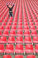 Female football fan alone in stadium