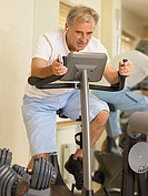 Man on an exercise bike listening to music