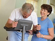 Man on exercise bike with his wife