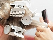 Hairdresser putting in curlers