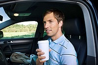 Man in car with coffee cup