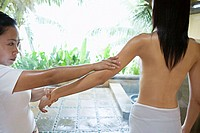 Masseuse holding womans arm