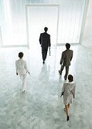 Four executives walking across lobby toward exit