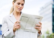 Businesswoman reading financial pages of newspaper