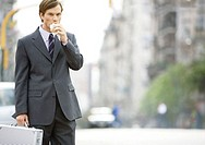 Businessman in the street, eating on the go