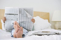 Man reading a newspaper in bed