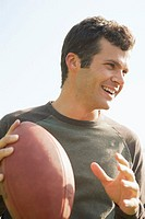 Man smiling and throwing football