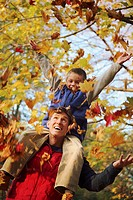 Young boy with his father, playing with leaves