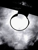 A playground basketball hoop is captured in sillouette against a dramatic sky