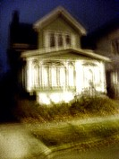 A green, nineteenth century house in upstate New York is captured at night in a ghostly blur. USA