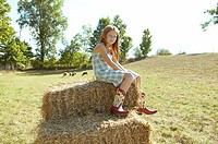 Girl sitting on a hay bale (thumbnail)