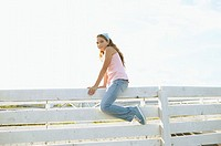 Girl sitting on top of a fence (thumbnail)