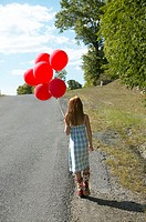 Girl carrying baloons beside a country road (thumbnail)