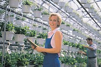 Florist in greenhouse, portrait.