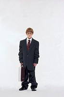Boy in oversized business suit, portrait.