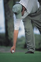 Man placing golf ball on tee.