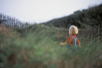 Boy running in grass.