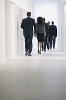 Business people walking down hallway.