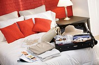 Woman´s luggage and travel brochures on bed.