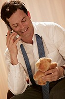 Businessman in hotel room holding teddy bear and talking on cell phone.