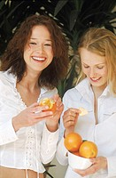Portrait of Two Young Women Eating Fruit