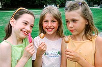 Young girls smiling holding lollipops