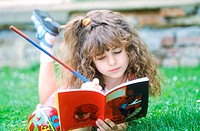 Young girl lying on lawn writing in book