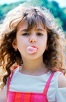 Young girl blowing chewing gum bubble (thumbnail)