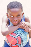 Young boy leaning his chin on a basketball