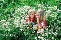 Two young children squatting in a bush