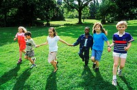 Young children holding hands running on a lawn
