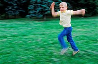 Young boy running on a lawn