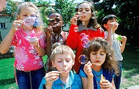 Young children blowing soap bubbles