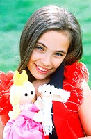 Portrait of a young girl holding dolls smiling