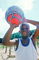 Young boy holding up a basketball