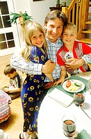 Father with children at the breakfast table