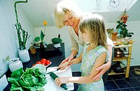 Grandmother helping granddaughter in the kitchen (thumbnail)