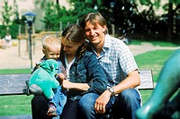 Father and mother holding baby and sitting on park bench