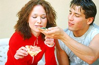 Man feeding a woman a slice of pizza