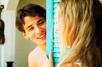 Young man looking at a woman from behind a door