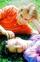Close-up of young couple lying in the grass together