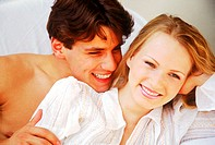 Young couple lying together smiling (thumbnail)