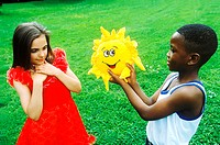 Young boy giving a young girl a toy stuffed sun flower