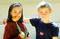 Portrait of a young girl holding a flower and a young boy smiling