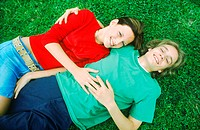 Portrait of young couple lying on the grass holding each other