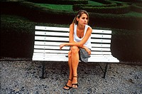 Young woman sitting on a park bench (thumbnail)
