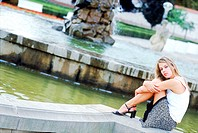Young woman sitting on a fountain wall outdoors (thumbnail)