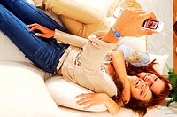 Two young women lying in bed looking at a mobile phone (thumbnail)