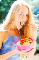 A young woman eating a bowl of salad