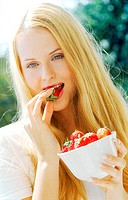 Portrait of a young woman eating strawberries